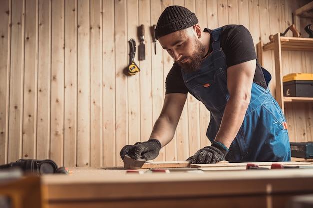 Erfahrener schreiner in arbeitskleidung und kleinunternehmer, der in einer holzwerkstatt arbeitet
