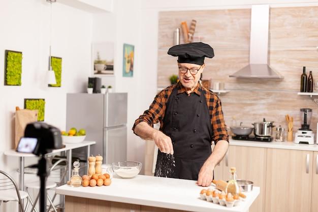 Erfahrener seniorchef-aufzeichnungs-tutorial mit lebensmittelzubereitung in der küche. pensionierter blogger-bäcker-influencer, der internet-technologie verwendet, um zu kommunizieren, zu schießen, zu bloggen in sozialen medien mit digitalem e