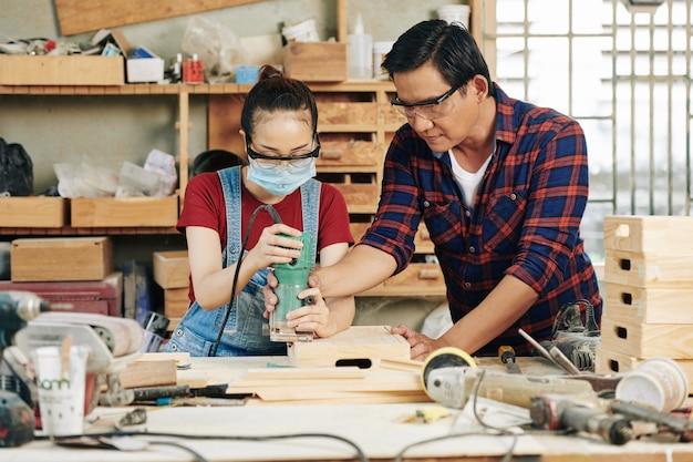 Erfahrener tischler, der dem lehrling hilft, holzkisten mit schleifwerkzeug zu polieren