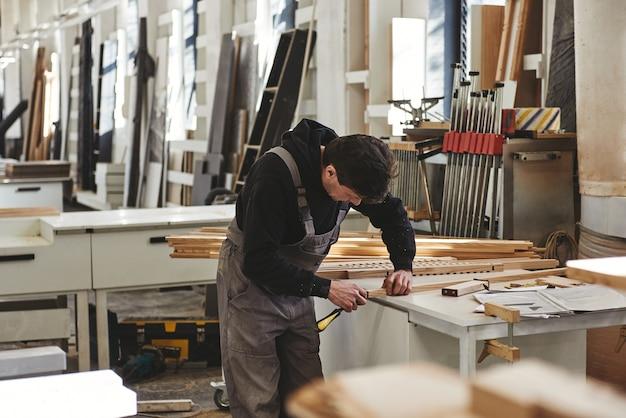 Erfahrener tischler in grauer uniform, der in seiner holzwerkstatt ein stück holz misst