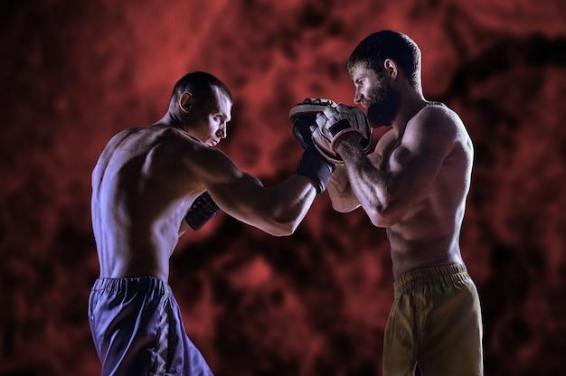 Erfahrener trainer bereitet einen jungen kämpfer vor. der kämpfer übt den unteren seitenaufprall aus und der trainer steht mit der auskleidung des armes