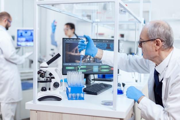 Erfahrener wissenschaftler, der in einem geschäftigen labor an seinem arbeitsplatz arbeitet und eine pipette hält. senior professioneller chemiker mit pipette mit blauer lösung für mikrobiologische tests.