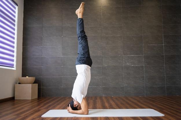 Erfahrener yogi, der unterstützte kopfstandyogahaltung tut
