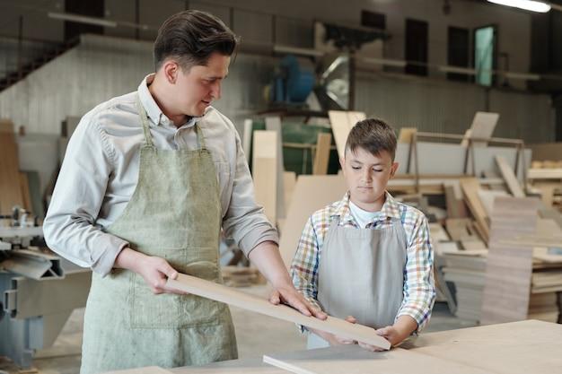 Erfahrener zimmermann in schürze, die holz berührt, während er sohn in der möbelwerkstatt verarbeitete planke zeigt