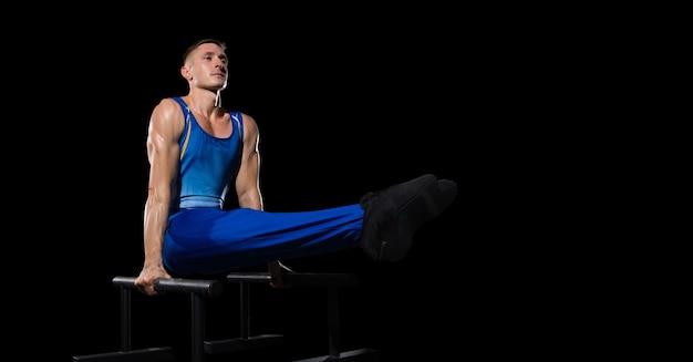 Erfahrung. muskulöses männliches turnertraining im fitnessstudio, flexibel und aktiv