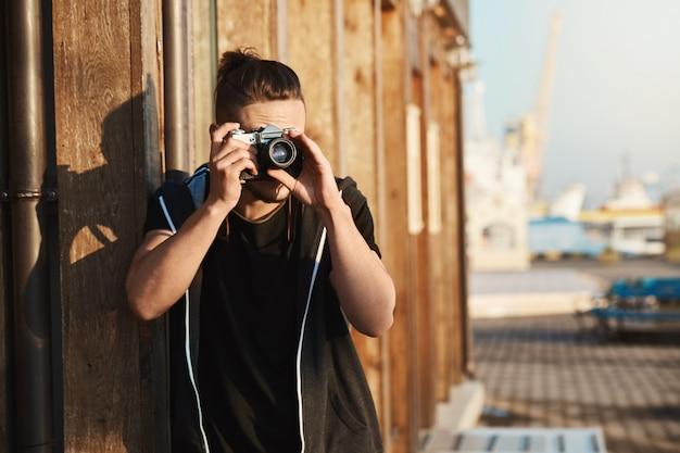 Erfassen sie jeden moment des lebens. außenaufnahme des jungen stilvollen fotografen, der durch weinlesekamera schaut, aufnahmen des hafens, der yachten und der küste macht und als freiberuflicher kameramann arbeitet