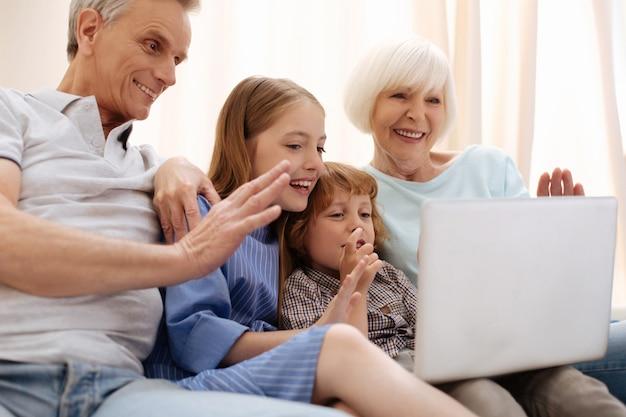 Erfinderische versierte charismatische geschwister, die mit mama und papa sprechen und über ihre schöne zeit erzählen, während sie ihre großeltern besuchen