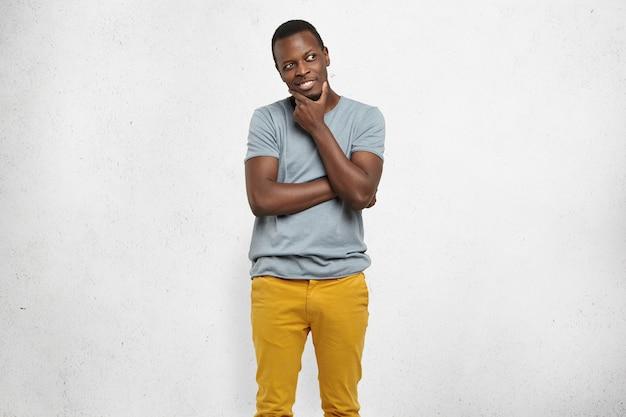 Erfinderischer hübscher afroamerikanischer mann, der mit schlauem lächeln wegschaut und hand auf seinem kinn hält