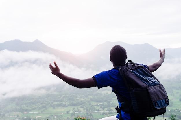 Erfolg afrikanische kletterer suchen auf der spitze des hügels mit nebel und regen bedeckt.