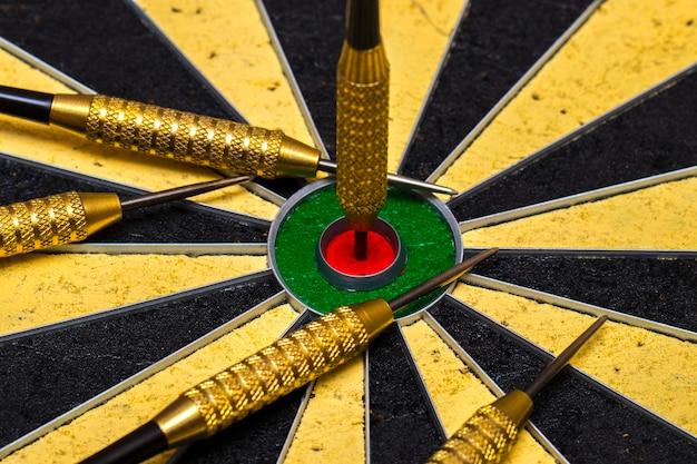 Erfolg beim erreichen des zielziels zielerreichungskonzepthintergrund - darts in bull's eye nahaufnahme