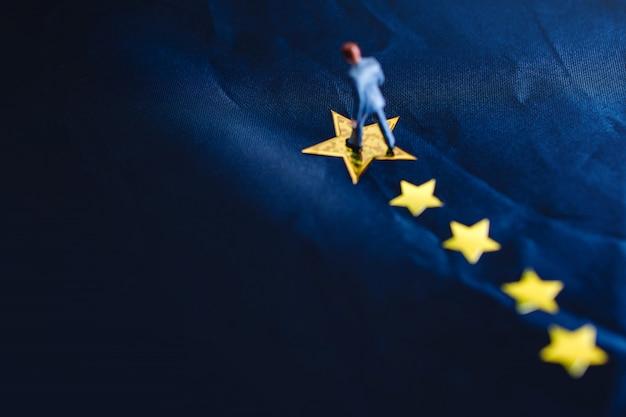 Erfolg im geschäft oder im talent-konzept. draufsicht eines miniaturgeschäftsmannes standing auf einem gelben goldenen stern