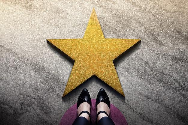 Erfolg im geschäftlichen oder persönlichen talentkonzept. draufsicht der geschäftsfrau in den arbeitsschuhen, die vor einem goldenen stern stehen