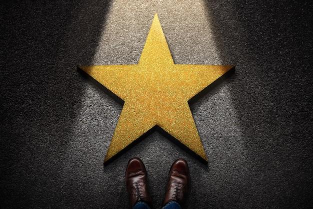 Erfolg im geschäftlichen oder persönlichen talentkonzept. draufsicht der geschäftsperson in arbeitsschuhen, die vor einem goldenen stern stehen