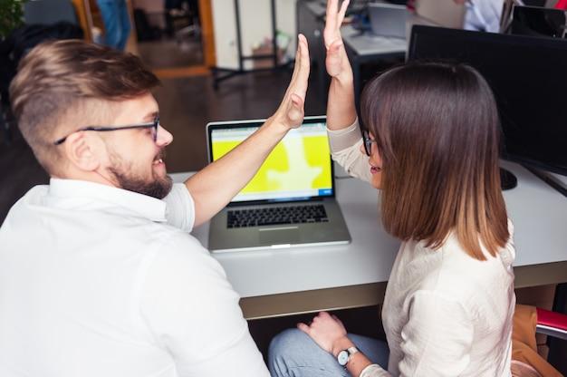 Erfolg junger mitarbeiter im büro. gib einander fünf