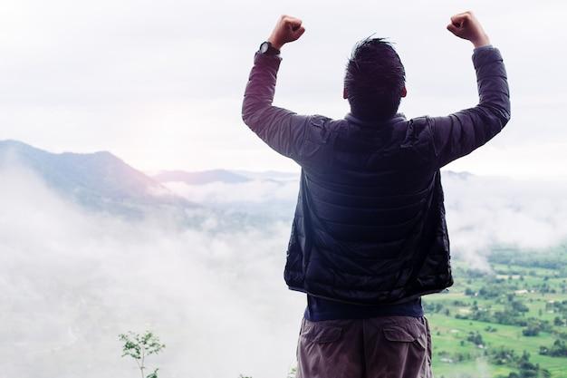 Erfolg kletterer stehen oben auf dem mit nebel bedeckten hügel.