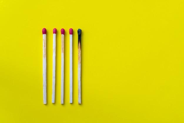 Erfolg, niederlage, leistung. das konzept des glücks. streichhölzer auf gelbem grund. verbranntes dunkles streichholz unter normalen streichhölzern. brennendes streichholzfeuer für seine nachbarn, eine metapher für ideen und inspiration