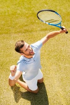Erfolge feiern. draufsicht eines glücklichen jungen mannes im polohemd, der tennisschläger hält und gestikuliert, während er auf dem tennisplatz kniet