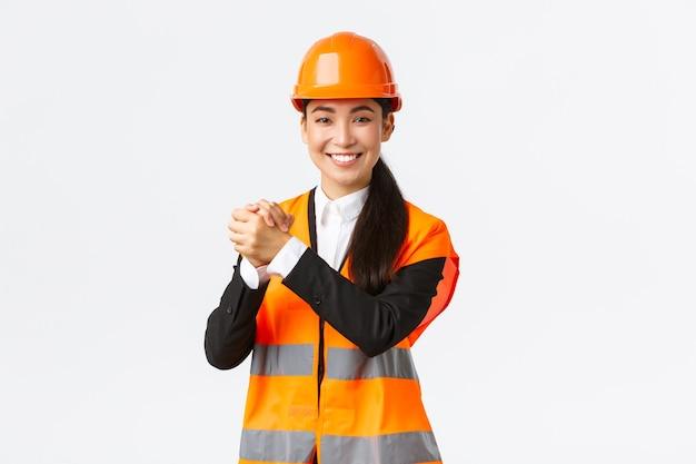 Erfolgreich gewinnende asiatische architektin händeschütteln, ziel erreichen. chief construction manager feiert sieg, abschluss der bauarbeiten, stehende weiße wand begeistert.