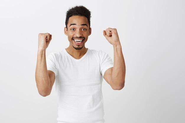 Erfolgreich gewinnender dunkelhäutiger kerl, der sich freut, die faust pumpt und lächelt, ja sagt und triumphiert