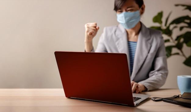 Erfolgreich während des coronavirus-konzepts. verschwommen fröhliche geschäftsfrau, die maske trägt und am laptop im büro arbeitet. computer im fokus