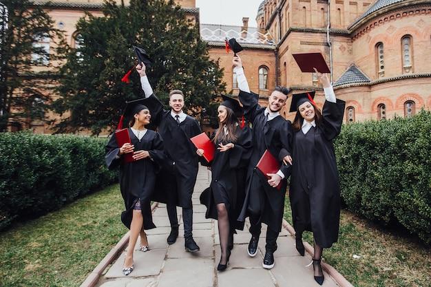 Erfolgreiche absolventen in akademischen kleidern halten diplome, betrachten kamera und lächeln bei draußen stehen. lebensstil