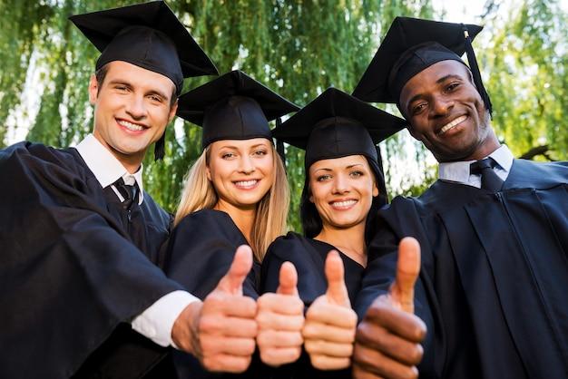 Erfolgreiche absolventen. niedrigwinkelansicht von vier hochschulabsolventen in abschlusskleidern, die nahe beieinander stehen und ihre daumen nach oben zeigen