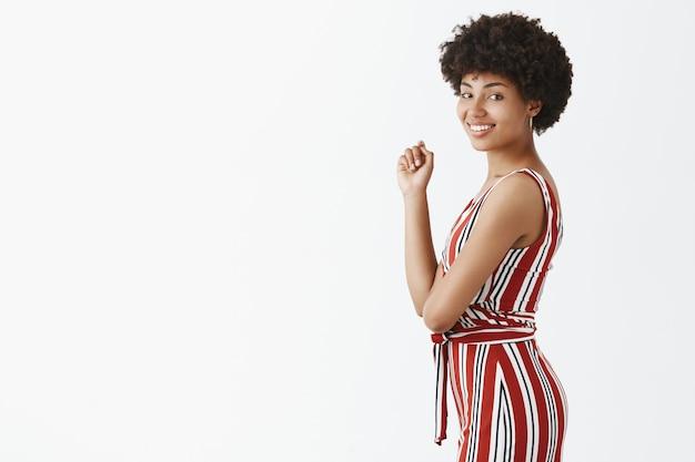 Erfolgreiche afroamerikanische geschäftsfrau in trendigen gestreiften overalls, die im profil stehen und sich mit einem breiten zufriedenen und glücklichen lächeln drehen und zeit für formelles treffen genießen