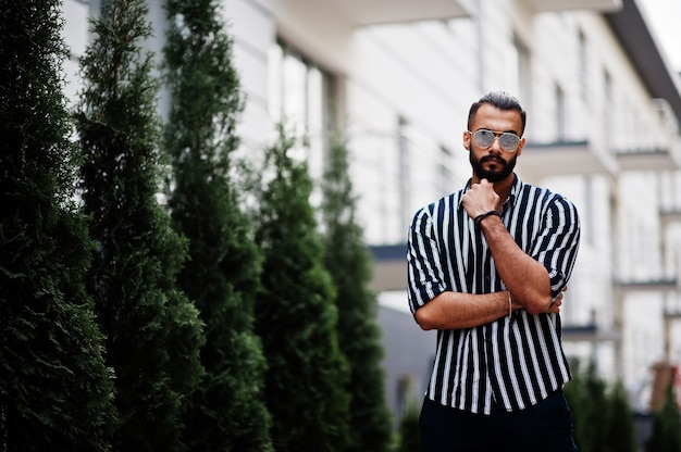 Erfolgreiche arabische mannkleidung im gestreiften hemd und in der sonnenbrille werfen im freien auf.