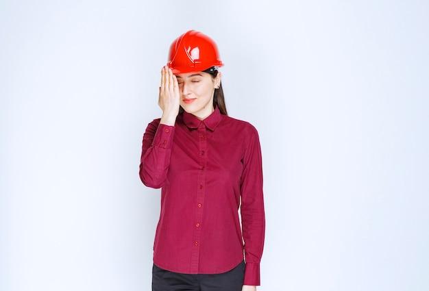 Erfolgreiche architektin im roten harten helm, der steht und posiert.