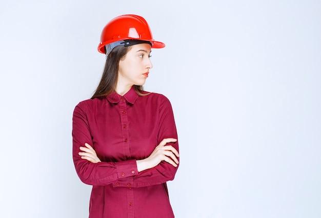Erfolgreiche architektin im roten harten helm, die ihre seite steht und schaut.