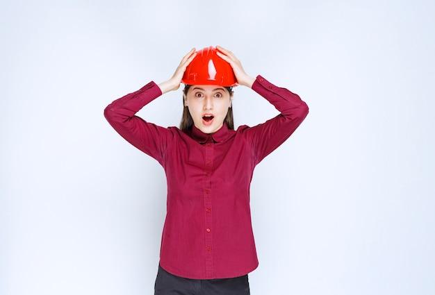 Erfolgreiche architektin im roten harten helm, die ihren kopf aus frustration hält.