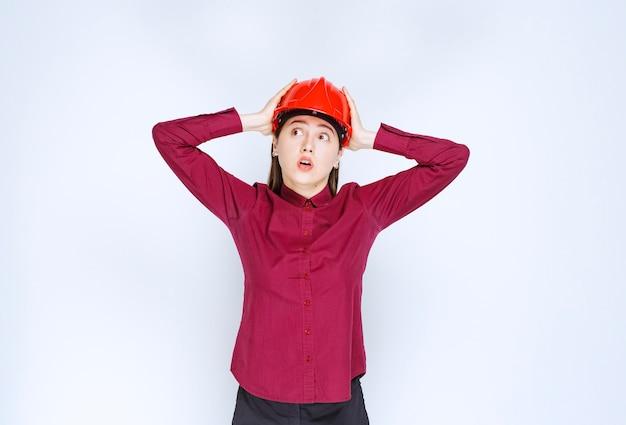 Erfolgreiche architektin im roten harten helm, die ihren kopf aus frustration hält. Kostenlose Fotos