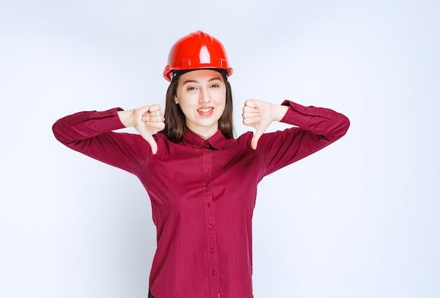 Erfolgreiche architektin im roten harten helm, die steht und daumen nach unten gibt.
