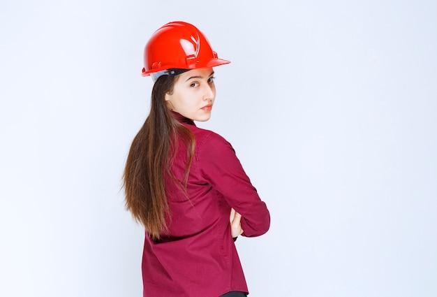 Erfolgreiche architektin im roten harten helm, die steht und schaut.