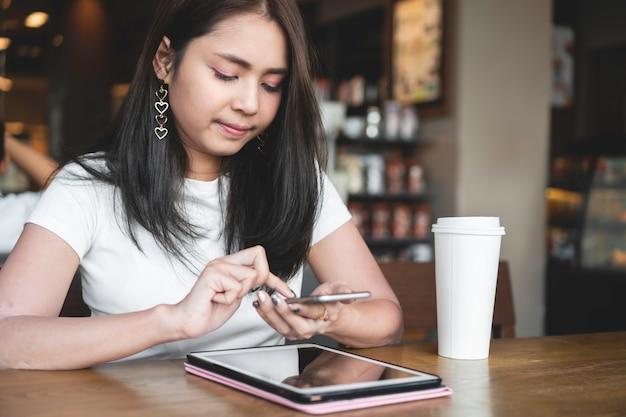 Erfolgreiche asiatische frau, die smartphone für onlinegeschäft am kaffeecafé verwendet.