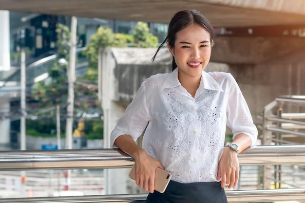 Erfolgreiche asiatische geschäftsfrau, die telefon hält und im freien steht.