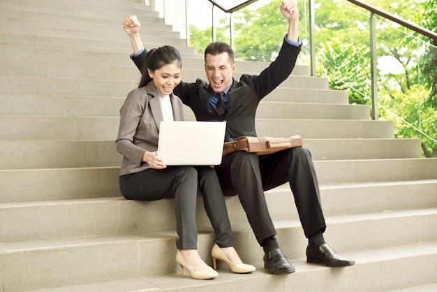 Erfolgreiche asiatische geschäftsleute mit dem laptop, der sehr glücklich schaut