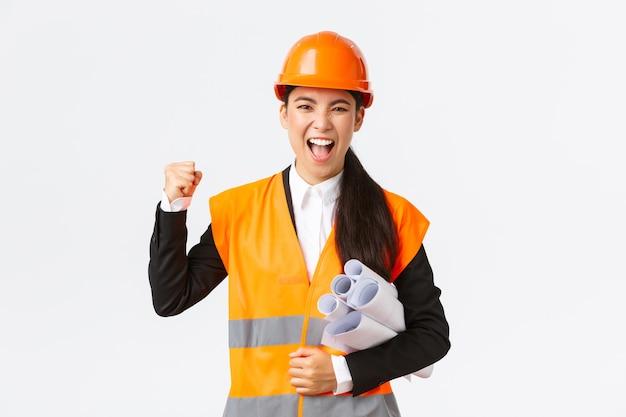 Erfolgreiche asiatische ingenieurin, architektin in schutzhelm und reflektierende jacke tragen blaupausen des bauprojekts und der faustpumpe zur feier, schreien ja, gewinnen zarte, weiße wand.