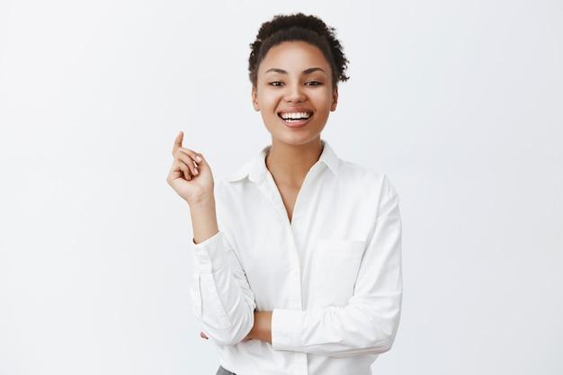 Erfolgreiche attraktive afroamerikanische geschäftsfrau, die mit zuversicht und gewagtem blick auf unternehmen blickt, die im wettbewerb verloren haben, vor freude laut lachen und triumphieren