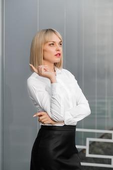 Erfolgreiche attraktive junge frau im weißen hemd und im schwarzen rock, die gegen grauen hintergrund steht.
