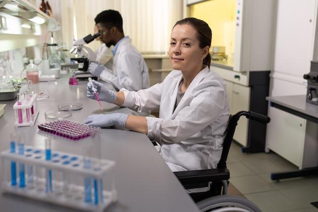 Erfolgreiche behinderte wissenschaftlerin im rollstuhl, die im labor arbeitet