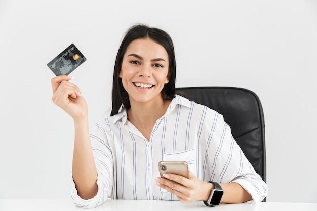Erfolgreiche brünette geschäftsfrau, die smartphone und plastikkreditkarte beim sitzen im sessel am tisch im büro lokalisiert über weißer wand hält
