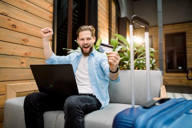 Erfolgreiche buchung, reise. kreditkarte in der hand des jungen mannes, der auf sofa sitzt