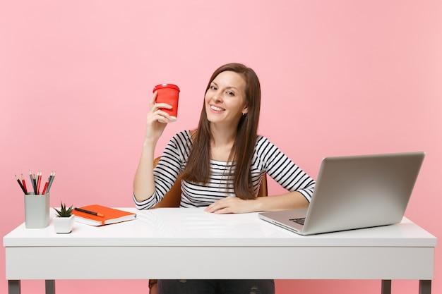 Erfolgreiche frau, die eine tasse kaffee oder tee hält und an einem projekt arbeitet, das im büro sitzt, mit einem pc-laptop einzeln auf pastellrosa hintergrund. erfolgsgeschäftskarrierekonzept. kopieren sie platz für werbung.