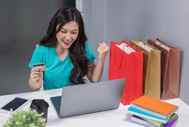 Erfolgreiche frau, die laptop-computer für das on-line-einkaufen mit kreditkarte verwendet