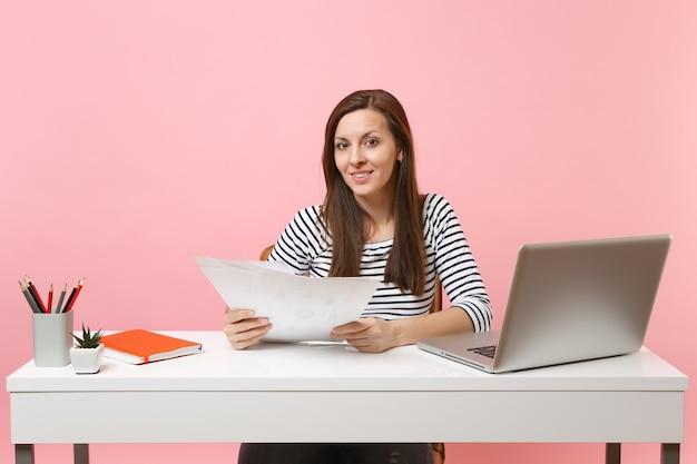 Erfolgreiche frau in freizeitkleidung, die papierdokumente hält, am projekt arbeitet, während sie mit laptop im büro sitzt sitting