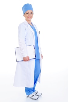 Erfolgreiche fröhliche chirurgin im krankenhauskleid mit dokumenten