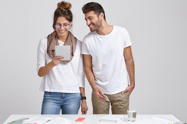 Erfolgreiche fröhliche sprecherin hält modernes touchpad