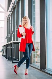 Erfolgreiche geschäftsdame in einem roten anzug in einem hellen bürogebäude am fenster
