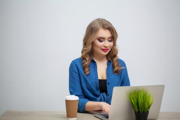 Erfolgreiche geschäftsfrau, die am computer im büro arbeitet.